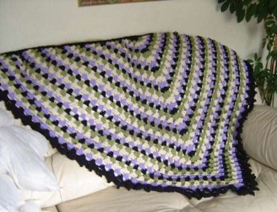 crochet shawl on couch 400x306 10 Crochet Shawls in Trees (and 8 Other Ways to Display your Finished Shawl)