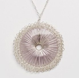 "Este es el collar de cuarzo rosa, uno de los varios que son similares en estilo. El sitio explica: ""Our round donut stones are wrapped with Miriam's signature crochet in fine silver or gold fill wire."""