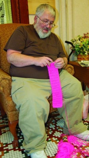 man crochets for breast cancer awareness