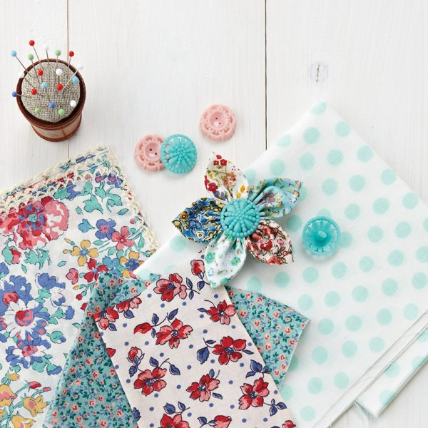 collection of vintage fabrics and flower broach on white wooden surface with min flower pot pin cushion No reproduction without permission. /m/loader/metro_loader/MMS39/MMS39.gift/